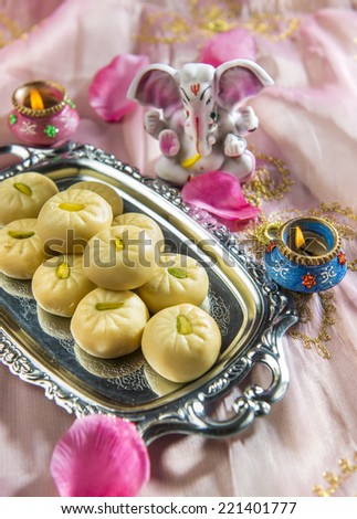 Indian sweets with tiny statue of Ganesha. - stock photo