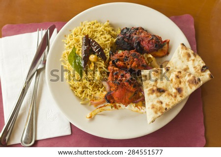 Indian tandoori chicken with fresh naan and tamarind rice - stock photo
