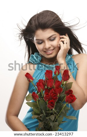 Indian teenage girl talking over cellphone with bunch of red roses - stock photo