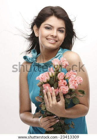 Indian teenage girl with happy expression carrying bunch of pink roses - stock photo