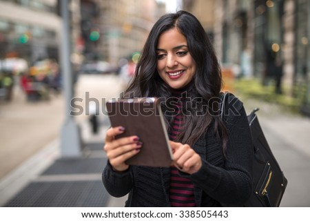 Indian woman in city walking using tablet computer - stock photo