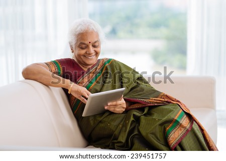 Indian woman in national dress sitting on the sofa and using a tablet - stock photo
