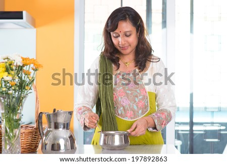 Indian woman preparing meal inside kitchen. Asian female cooking food at home. - stock photo