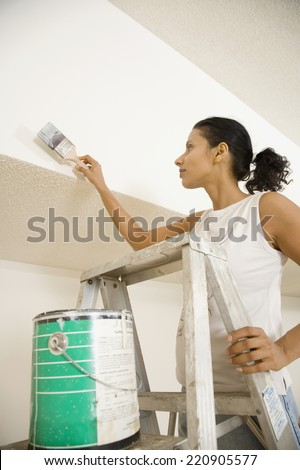 Indian woman standing on ladder painting - stock photo