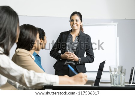 Indian woman standing up doing a presentation at a business meeting. - stock photo