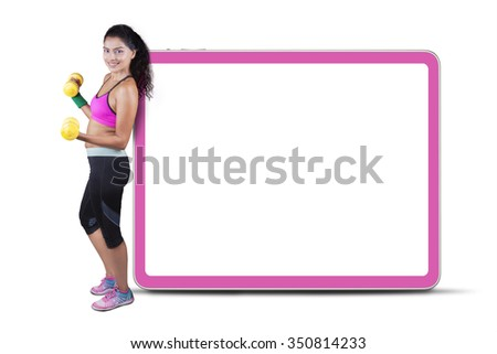 Indian woman wearing sportswear and holding two dumbbells while leaning on empty board - stock photo