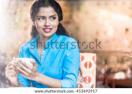 Indian woman with coffee mug and flirty expression - stock photo