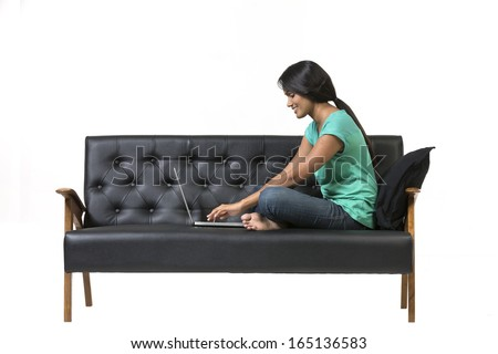 Indian Woman working on a laptop. Isolated over a white background - stock photo