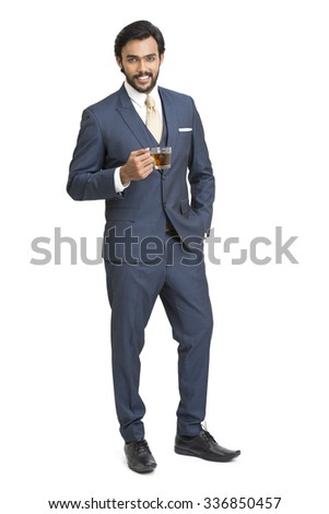 Indian young businessman posing with black tea on white. - stock photo