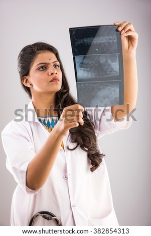indian young medical practitioner examining xray or MRI scan, indian female doctor and x ray or MRI, asian doctor checking xray or x ray, isolated on gray background  - stock photo