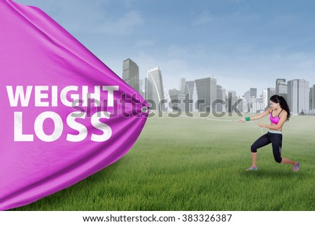 Indian young woman pulls a big flag with weight loss text at field while wearing sportswear - stock photo