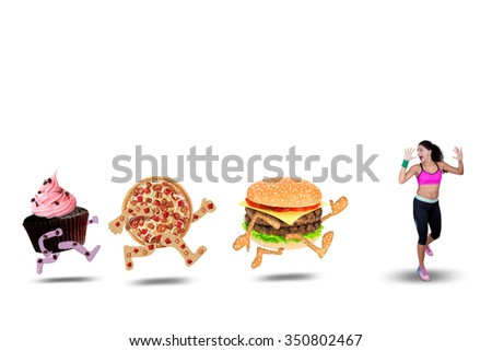 Indian young woman running away from junk food while wearing sportswear, isolated on white background - stock photo