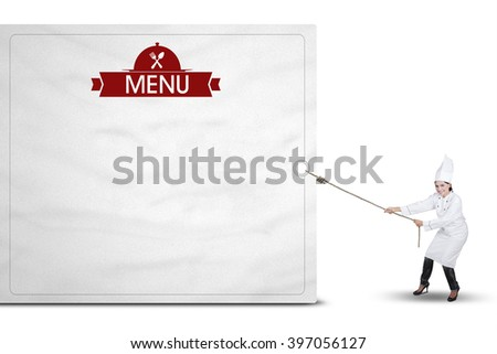 Indian young woman wearing a chef uniform and pulls a big billboard with a menu text - stock photo
