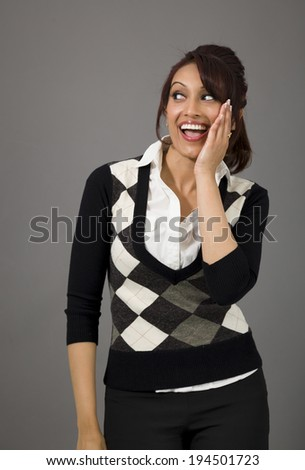 Indian young woman whispering message isolated on colored background - stock photo