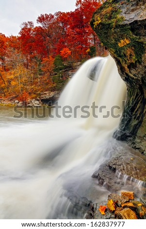 Indiana's Upper Cataract Falls is photographed  with intensely colorful fall foliage on the surrounding cliffs. - stock photo