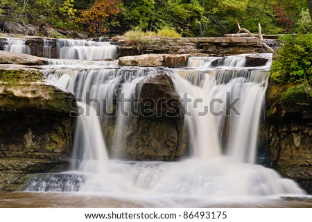 Indiana's Upper Cataract Falls pouring whitewater through boulders and over the edge. - stock photo