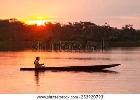 INDIGENOUS ADULT MAN WITH CANOE ON LAGOON GRANDE, CUYABENO NATIONAL PARK, ECUADOR AT SUNSET, MODEL RELEASED  - stock photo