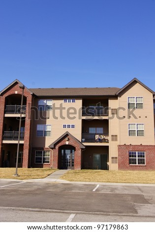 Individual apartment complex building near parking lot - stock photo