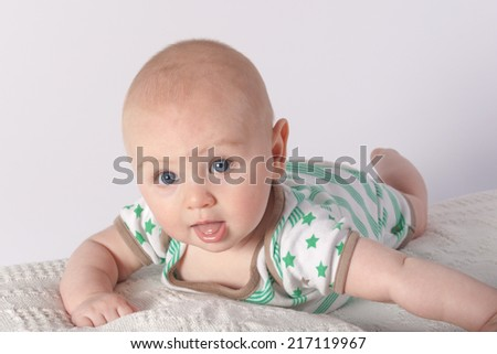 Individual baby with sweet expression pushing to lift head  - stock photo