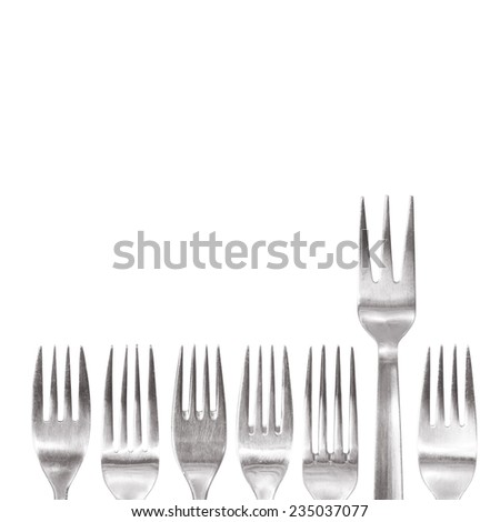 individual fork with three spikes standing out of the crowd of different shaped normal cutlery. special restaurant concept - stock photo