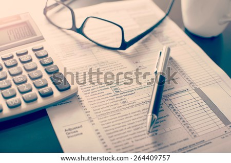 Individual income tax return form, glasses, pen and calculator on desk - stock photo