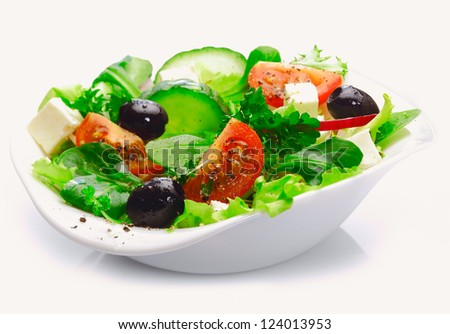 Individual side serving of delicious fresh Greek salad with feta cheese, olives, tomatoes and salad greens - stock photo