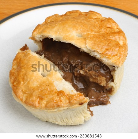 Individual steak meat pie cut open. - stock photo