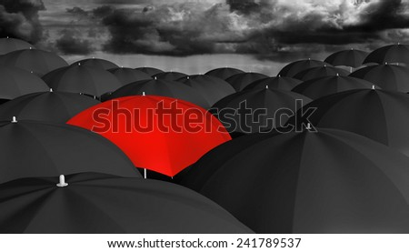Individuality and thinking different concept of a red umbrella in a crowd of black ones - stock photo