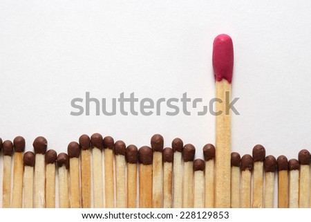 Individuality concept. One big match between row of ordinary small matches on white background - stock photo