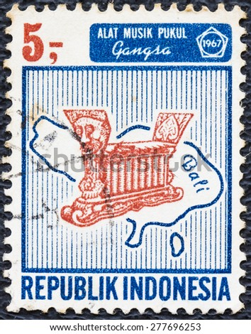 INDONESIA - CIRCA 1967 : A used postage stamp  printed in Indonesia shows Indonesian islands and musical instruments, circa 1967 . Indonesian islands and musical instruments - stock photo