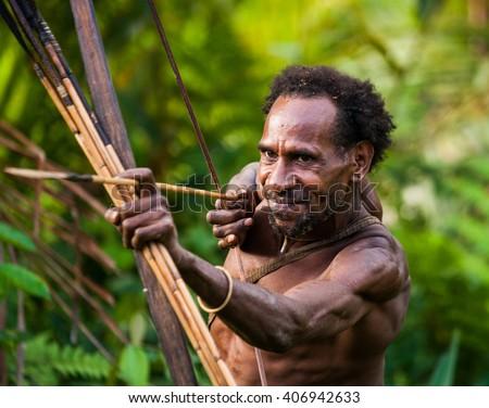 INDONESIA, ONNI VILLAGE, NEW GUINEA - JUNE 24: Man Korowai tribe shoots a bow. Tribe of Korowai (Kombai , Kolufo).On June 24, 2012 in Onni Village, New Guinea, Indonesia - stock photo