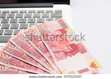 Indonesia Rupiah currency on laptop - stock photo
