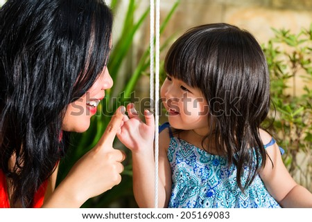 Indonesian Asian Little girl and her mother in the garden playing on a swing - stock photo