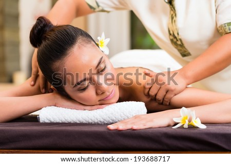 Indonesian Asian woman in wellness beauty day spa having aroma therapy massage with essential oil, looking relaxed - stock photo
