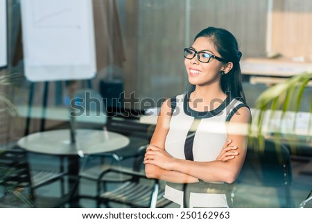 Indonesian business woman at office window - stock photo