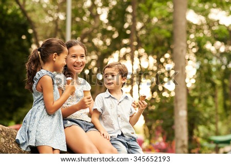 Indonesian children talking and eating ice-cream in the park - stock photo
