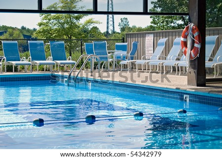 indoor and outdoor swimming pool with chairs - stock photo