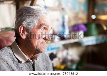 Indoor closeup portrait of an expressive senior farmer with selective focus - stock photo