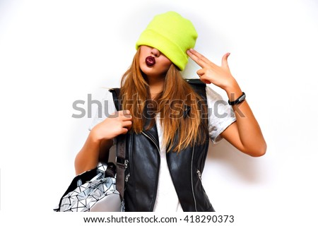 Indoor fashion grunge portrait of cheeky hipster girl ,leather jacket, rock style, dark lips, flash, white background, crazy emotions. Put hat on her eyes, imitating gun by her hand, angry, evil. - stock photo