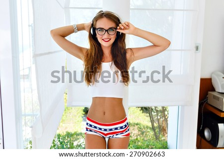 Indoor fashion lifestyle portrait of young sexy dj girl wearing sexy shorts with american symbolics, hipster vintage glasses and crop top, listening music on earphones and having fun.  - stock photo
