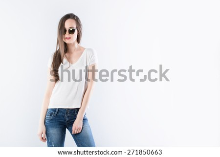 Indoor fashion portrait of young beautiful woman in t-shirt, jeans and sunglasses - stock photo