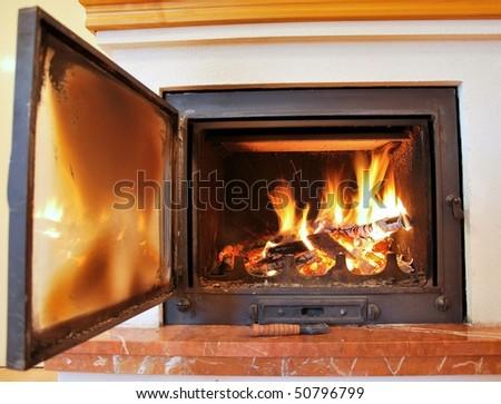 Indoor fireplace with open door. - stock photo