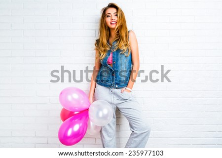 Indoor image on young trendy hipster blonde woman playing with pink balloons, ready for party. Urban white background, positive emotions. - stock photo