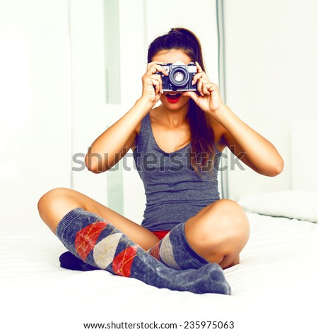 Indoor lifestyle image of pretty hipster girl taking photos on her vintage camera, wearing pajama sitting on big white bed. Instagram colors. - stock photo