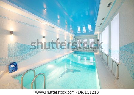 Indoor pool with images of dolphins at bottom and clear water in big room. - stock photo