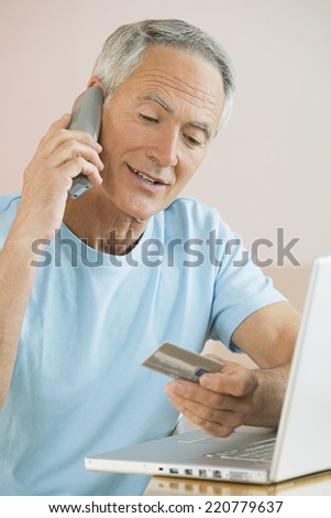 Indoor portrait of casually dressed senior man with credit card, telephone and laptop - stock photo