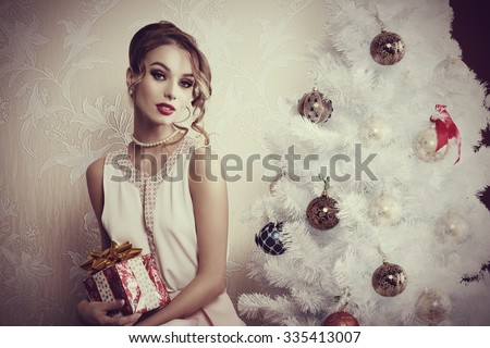 indoor portrait of elegant woman with make-up and hair-style posing near decorated Christmas tree with gift box in the hand - stock photo