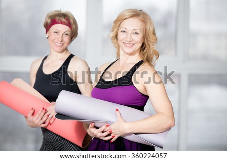 Indoor portrait of group of two cheerful attractive fit senior women posing holding fitness mats, working out in sports club class, happy smiling, looking at camera with friendly expression - stock photo