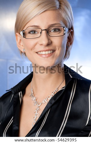 Indoor portrait of happy young businesswoman standing on office corridor, smiling. - stock photo