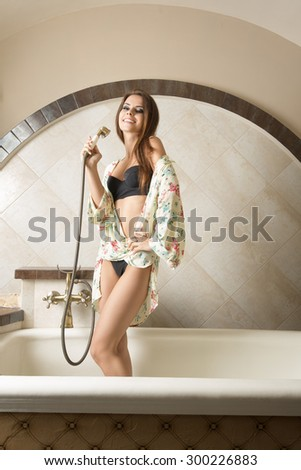 indoor portrait of sexy girl with black lingerie and large floral shirt posing in elegant bathroom with rustic retro style in bathtub with shower head in the hand, smiling and looking in camera  - stock photo